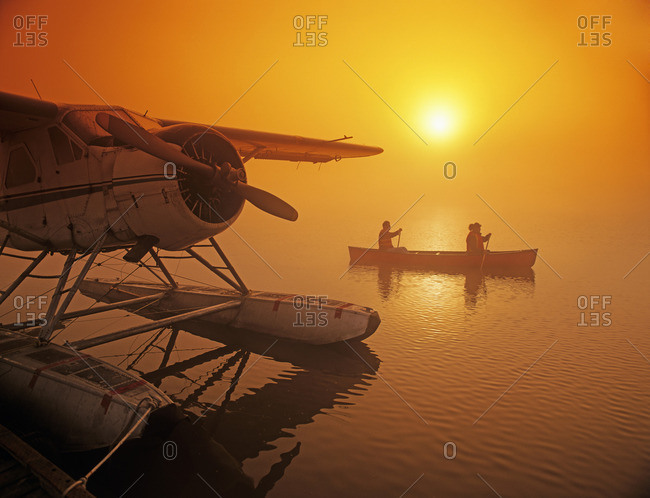 Manitoba, Canada - March 19, 2013: Couple canoeing in early morning mist near float plane dock