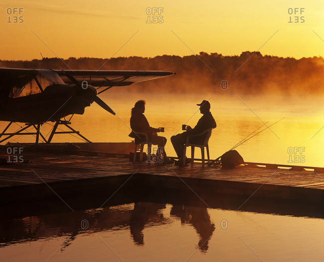 Manitoba, Canada - March 19, 2013: A couple relaxes on a float plane dock