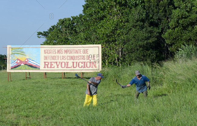 Cuba. - October 14, 2013: Cutting roadside grasses manually, with revolutionary sign