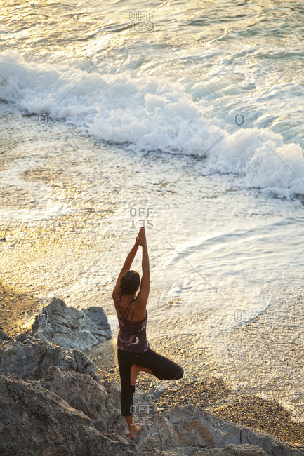 A young woman doing yoga at sunset near the beach in Kalymnos, Greece