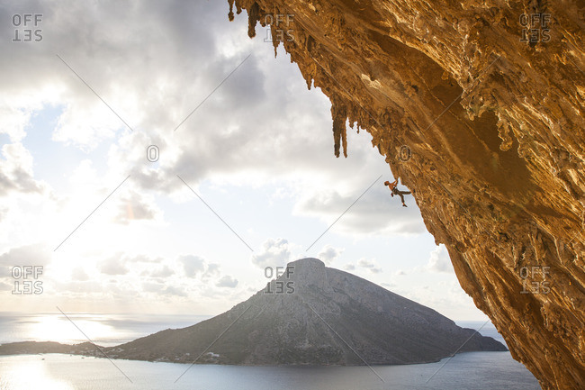 A male climber ascends through the wild limestone rock formations in the enormous cave of Grand Grotto, Kalymnos, Greece