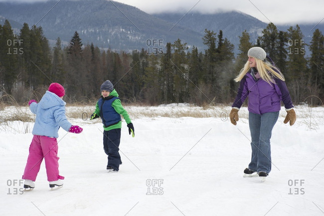 British Columbia, Canada - February 2, 2014: A family and their dog enjoy ice skating at 'The Marsh' near Valemount, Thompson Okanagan region