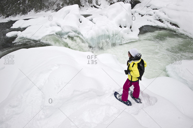 British Columbia, Canada - January 12, 2014: A young lady stops to check out 'Mushbowl Falls' in Wells Gray Provincial Park, Thompson Okanagan region