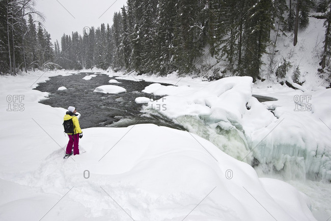 British Columbia, Canada - January 12, 2014: A young woman snowshoes past Mushbowl Falls in Wells Gray Provincial Park, Thompson Okanagan region
