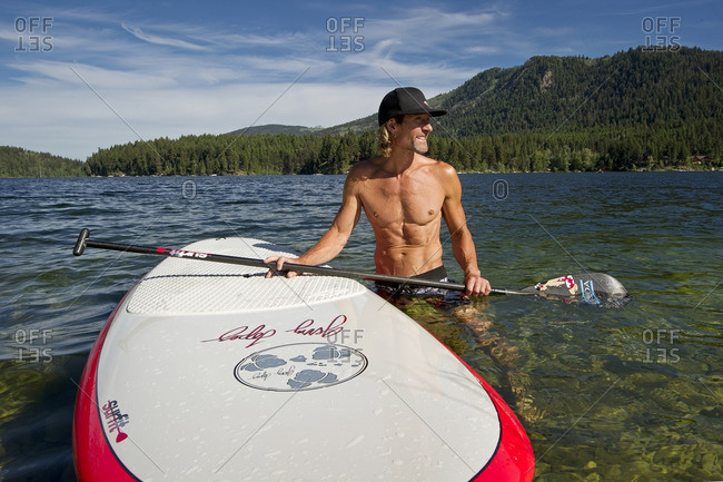 Heffley Lake, Thompson Okanagan, British Columbia, Canada - July 26, 2013: A professional paddle boarder stops for a break while enjoying the tropical like waters of Heffley lake, North of Kamloops in the Thompson Okanagan region