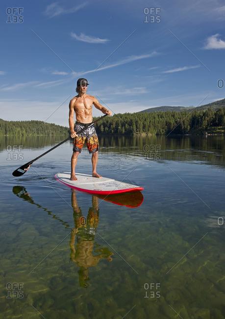 Heffley Lake, Thompson Okanagan, British Columbia, Canada - July 26, 2013: A paddle boarder enjoys a gorgeous day while on Heffley Lake, North of Kamloops in the Thompson Okanagan region