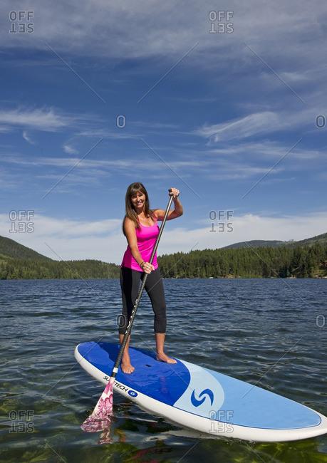 Heffley Lake, Thompson Okanagan, British Columbia, Canada - July 26, 2013: A female paddle boarder makes her way across the waters of Heffley Lake, North of Kamloops in the Thompson Okanagan region