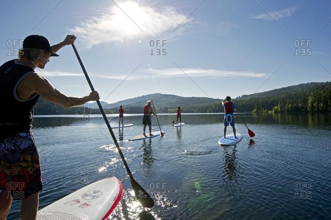 Heffley Lake, Thompson Okanagan, British Columbia, Canada - July 26, 2013: A group of paddle boarders make their way across the waters of Heffley Lake, North of Kamloops in the Thompson Okanagan region