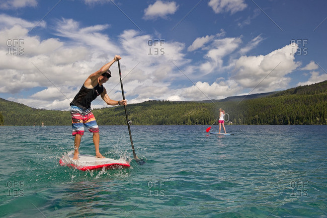 Thompson Okanagan, British Columbia, Canada - August 16, 2013: A professional paddle boarder makes his way across the tropical waters of Johnson Lake, North of Kamloops in the Thompson Okanagan region