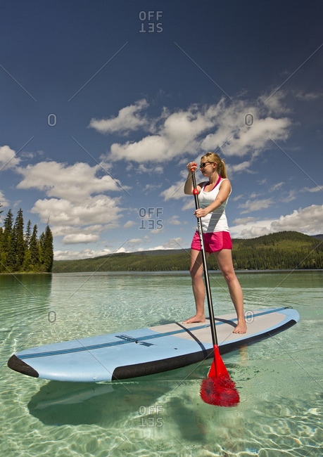 Thompson Okanagan, British Columbia, Canada - August 16, 2013: A young, attractive paddle boarder makes her way across the stunning waters of Johnson Lake, North of Kamloops in the Thompson Okanagan region