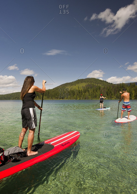 Thompson Okanagan, British Columbia, Canada - August 16, 2013: A group of paddle boarders make their way across the tropical like waters of Johnson Lake, North of Kamloops in the Thompson Okanagan region
