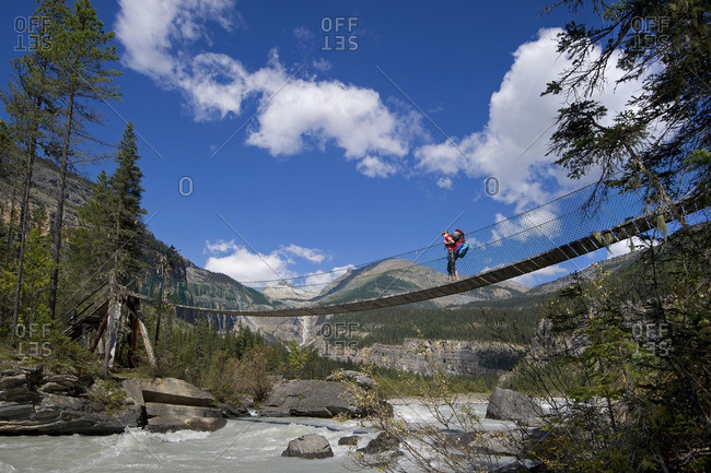 British Columbia, Canada - September 8, 2013: An attractive young lady takes in the views of the Robson River while crossing the White Falls bridge on the Robson trail system of Mount Robson, just North of Valemount, in the Thompson Okanagan region