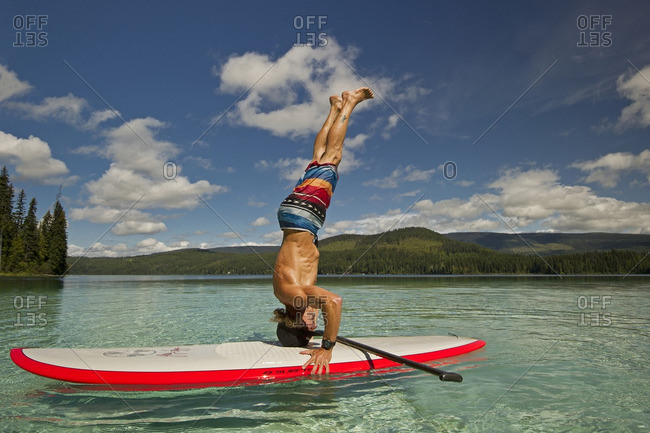 Thompson Okanagan, British Columbia, Canada - August 16, 2013: A paddle boarder practices yoga on the beautiful waters of Johnson Lake, North of Kamloops in the Thompson Okanagan region
