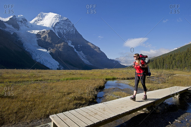 British Columbia, Canada - September 8, 2013: A young lady hikes the Robson trail system with the Berg Glacier and Mount Robson in the background, just North of Valemount, in the Thompson Okanagan region