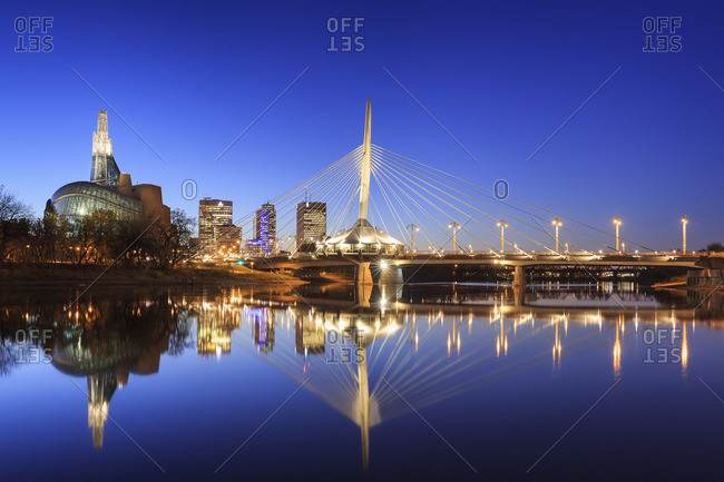Winnipeg, Manitoba, Canada - October 20, 2014: Skyline of Winnipeg at night with Canadian Museum for Human Rights and Esplanade Riel Bridge reflected in the Red River