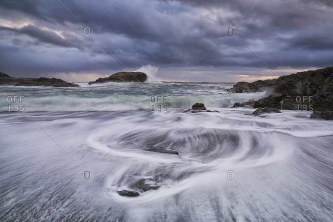 Water flows around the rocks of South Beach as high tide approaches, Pacific Rim National Park, British Columbia, Canada Waves smash against the rocks as a storm passes offshore