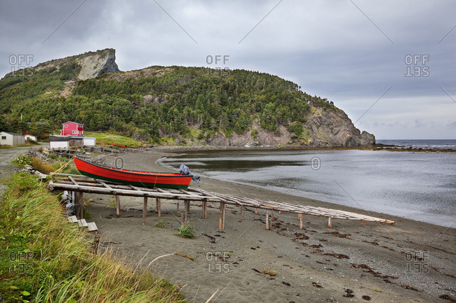 Located on the west coast of Newfoundland, Bottle Cove opens directly into the Gulf of Saint Lawrence and is renowned for its rugged, pristine beauty In the foreground, on a timber ramp, is a Lark Harbor dory built locally and characterized by its flat bottom and dark red coloration