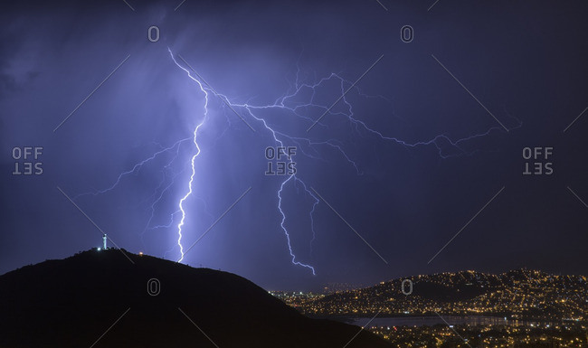 Lightning during a thunderstorm over the city of Cochabamba, Bolivia El Cristo is in the foreground