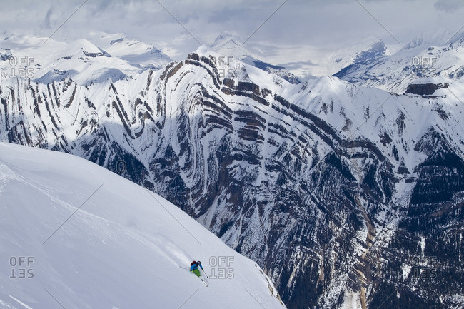 Young male skier  skis untracked powder in front the Sullivan Fault, Chatter Creek Catskiing, near Golden, BC, Canada