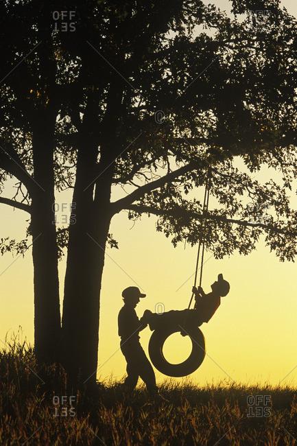 boys playing on tire swing under oak tree, Birds Hill Provincial Park, Manitoba, Canada