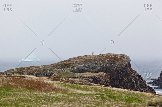 Hiker stopped to view an iceberg that is floating close to fog-bound shore in Elliston, Newfoundland