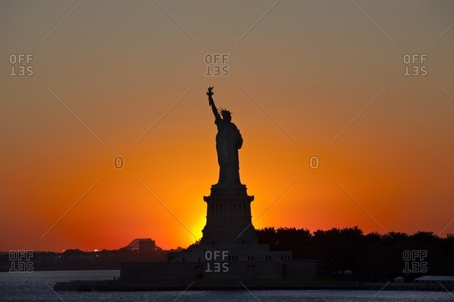 Silhouetted Statue of Liberty photographed against the setting sun Liberty Island, New York, USA