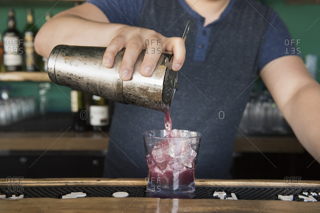 Man pouring a purple cocktail into a glass
