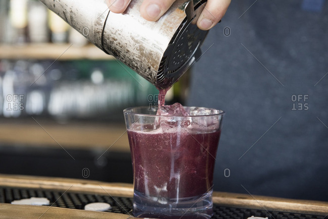 Bartender pouring a purple drink into a glass
