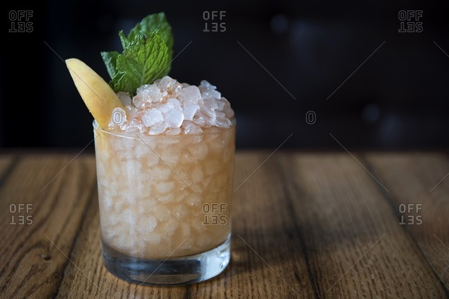 Cocktail over crushed ice garnished with mint and fruit