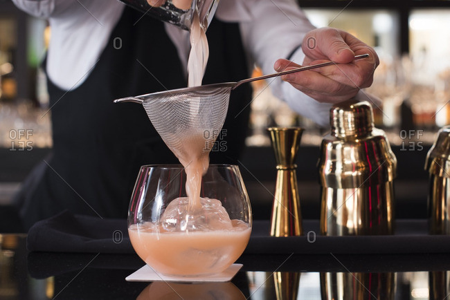 Bartender straining a pink drink into a glass