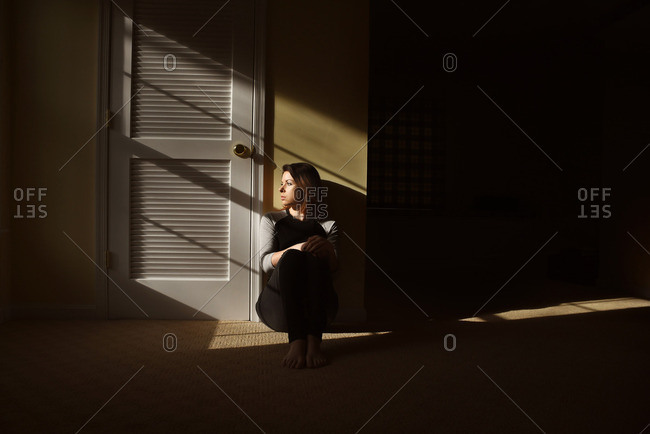 Woman sits alone in a room with light patterns