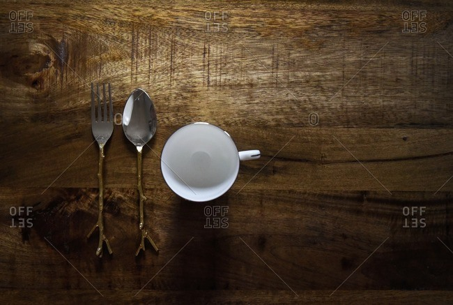 A teacup, fork, and spoon sit on large wooden table