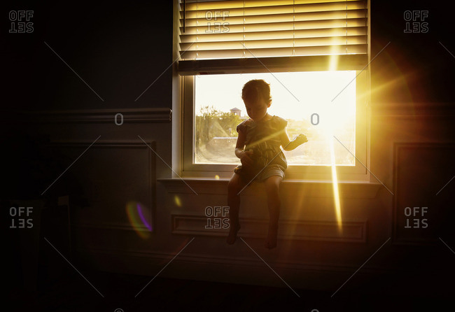 Girl sits on window ledge with light streaming through