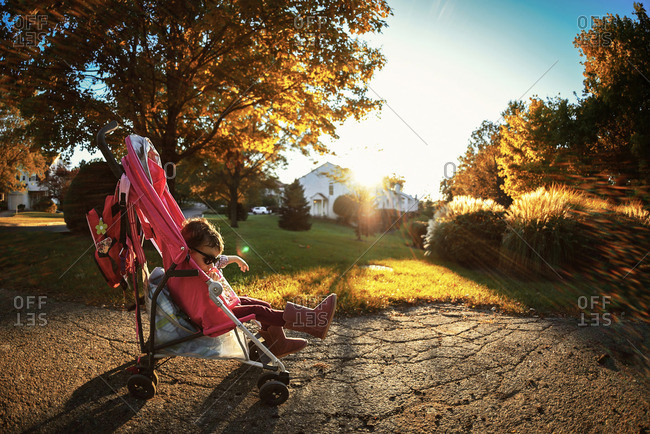 Young girl sitting in stroller at sunset
