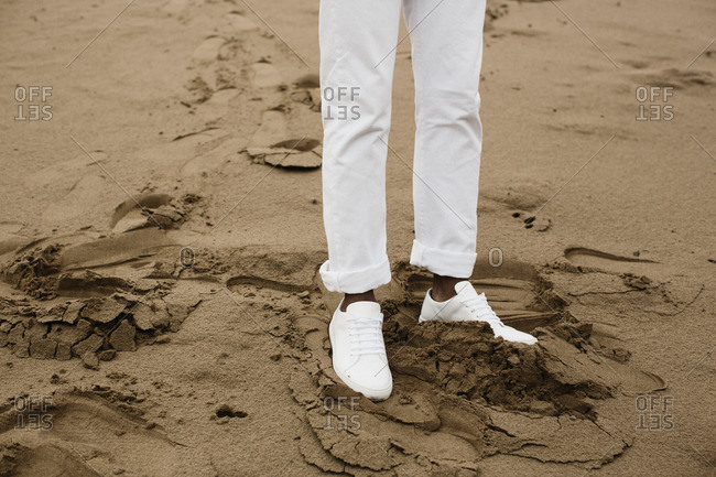 Man in white pants standing on sand