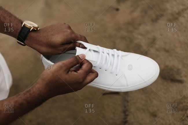 Man holding white shoe over beach