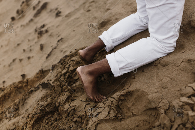 Man in bare feet lying on sand