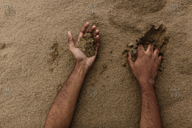 Hands digging in sand