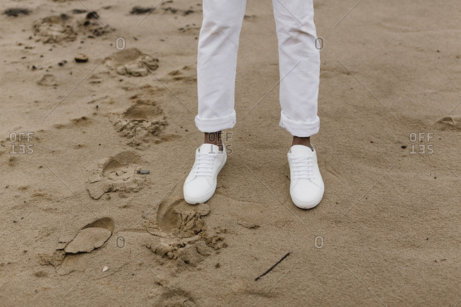 Person in white shoes standing on sand