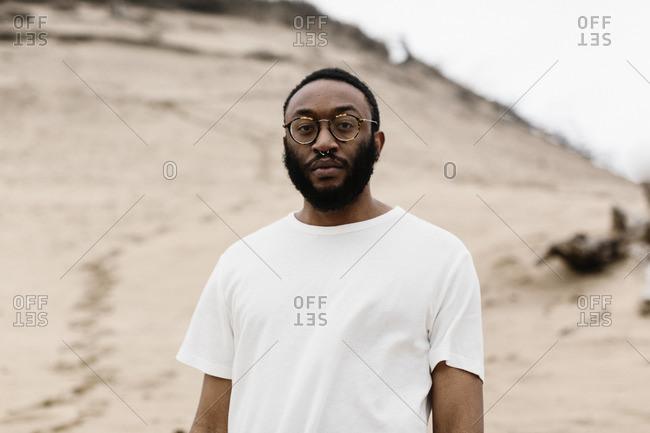 Hip man in white shirt on beach