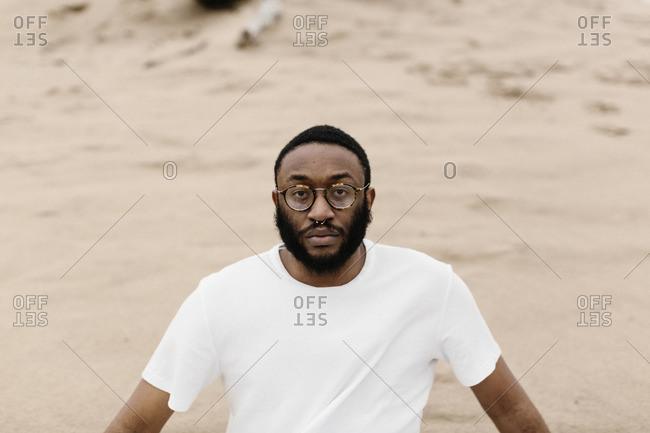 Hip man in a white shirt on beach