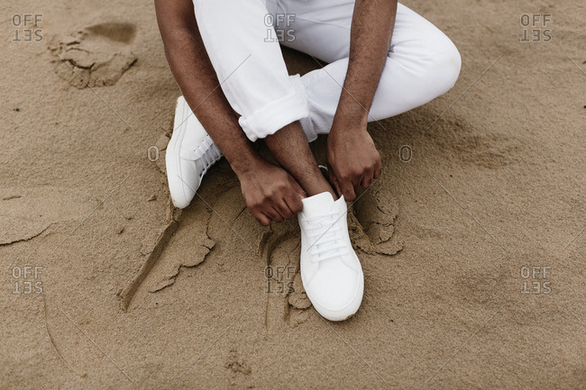 Man putting on white shoes on beach