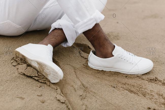 Man in white sitting in sand