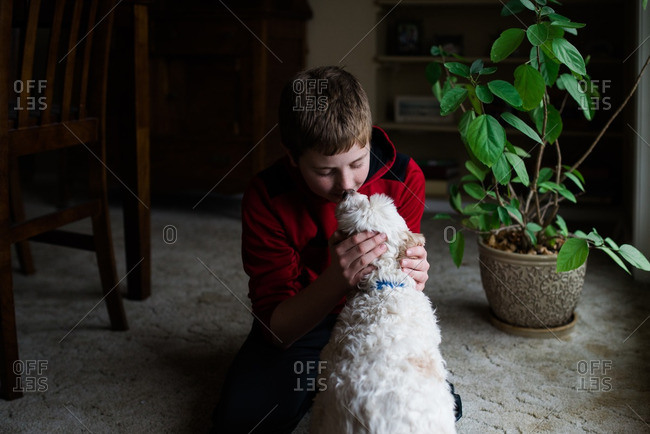 Boy sitting on a floor giving his dog a kiss