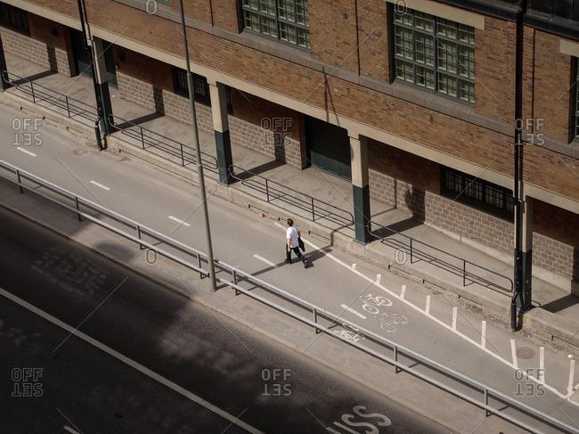 Man walking in a bike lane on an empty city street