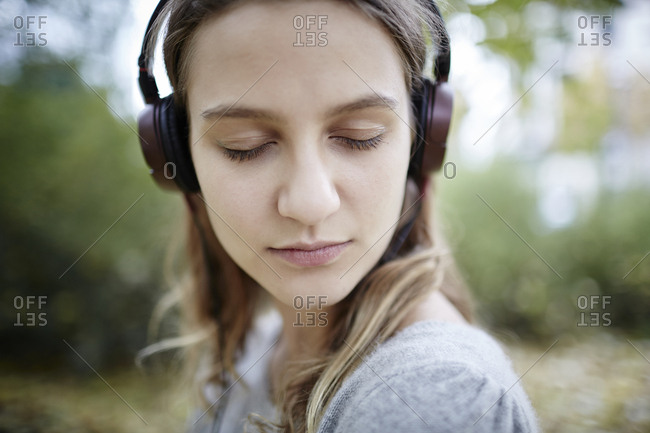 Young woman with closed eyes wearing headphones