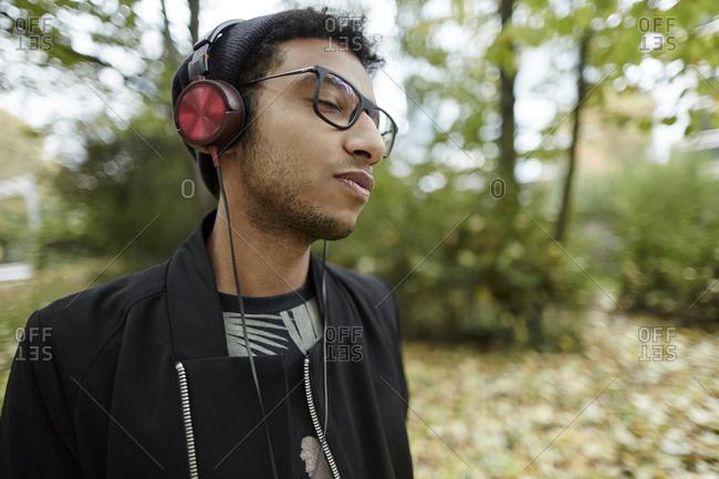 Young man wearing headphones in park