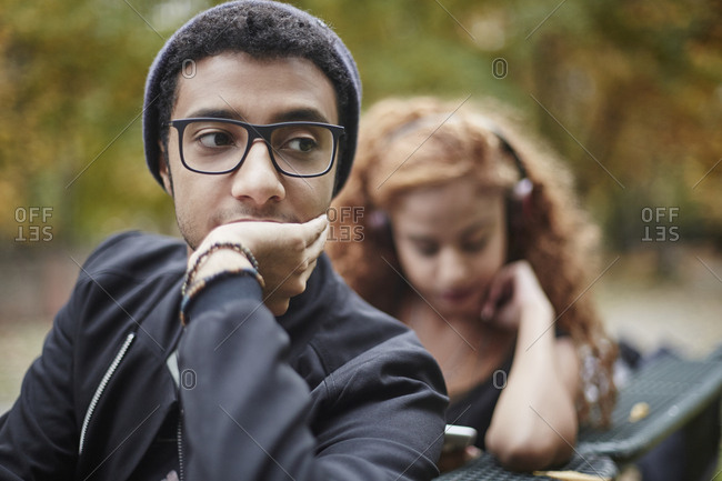 Serious young man on park bench with girlfriend in background