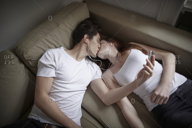 Young couple lying on couch listening to music and kissing