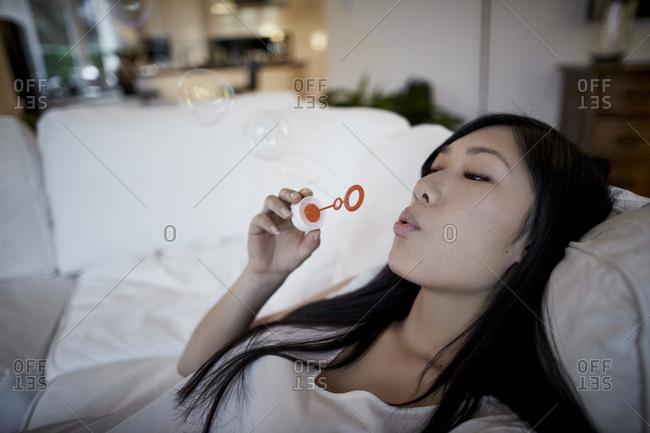 Woman on couch blowing soap bubbles